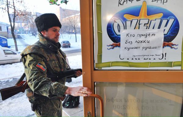Donetsk, un milicien rentre au Café Océan, qui nourrit gratuitement ceux qui en ont besoin